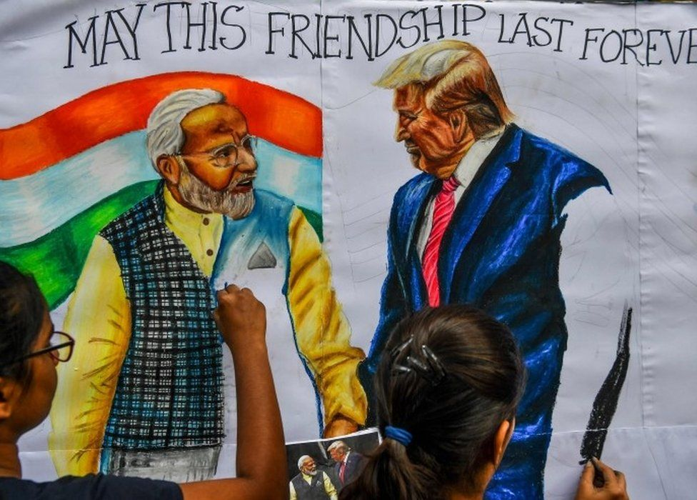 Students paint on canvas faces of US President Donald Trump (R) and India's Prime Minister Narendra Modi, in the street in Mumbai on February 21, 2020, ahead of the visit of US President in India