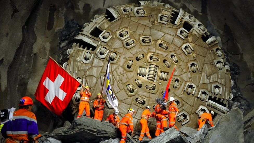 Miners celebrate after a giant drilling machine completed the world's longest tunnel beneath the Swiss Alps