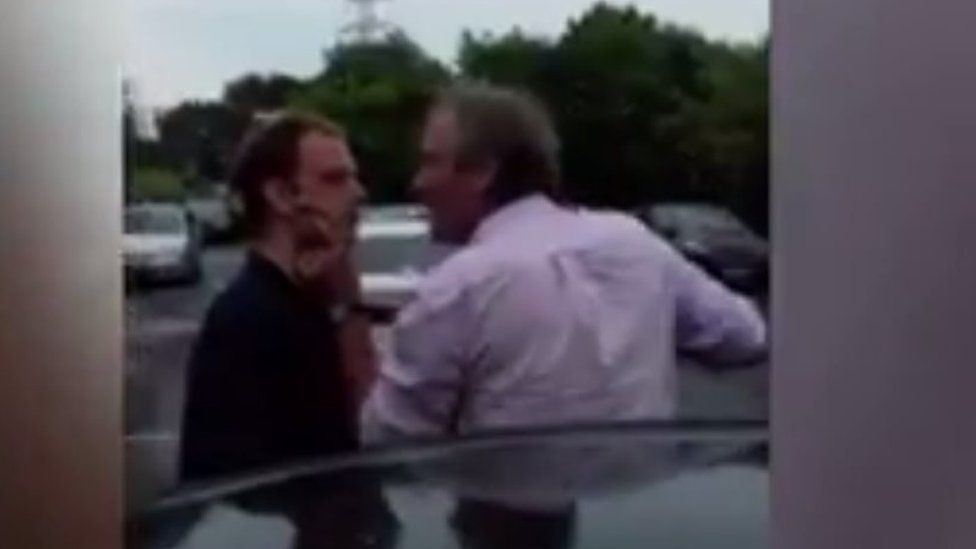 A man is held around the neck while another man threatens him
