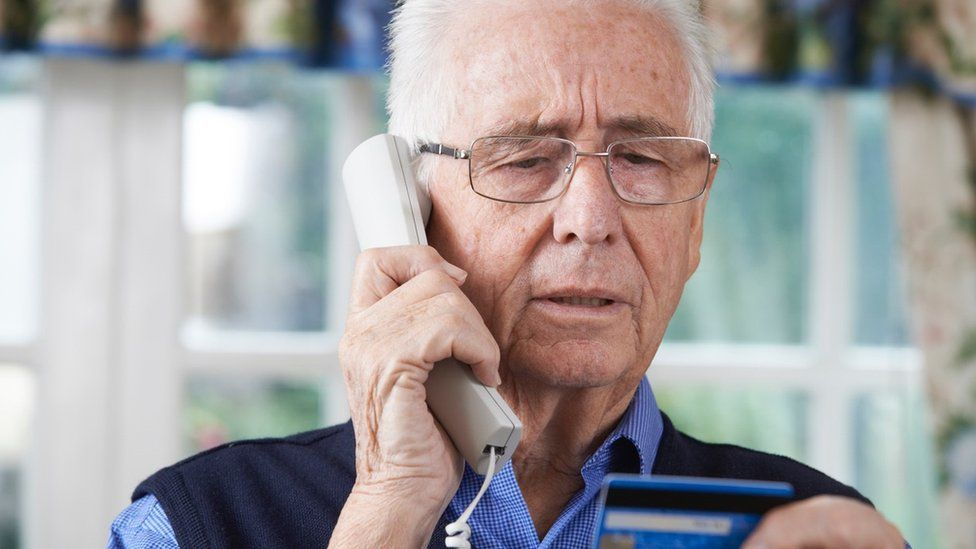 older man on phone with credit card in hand