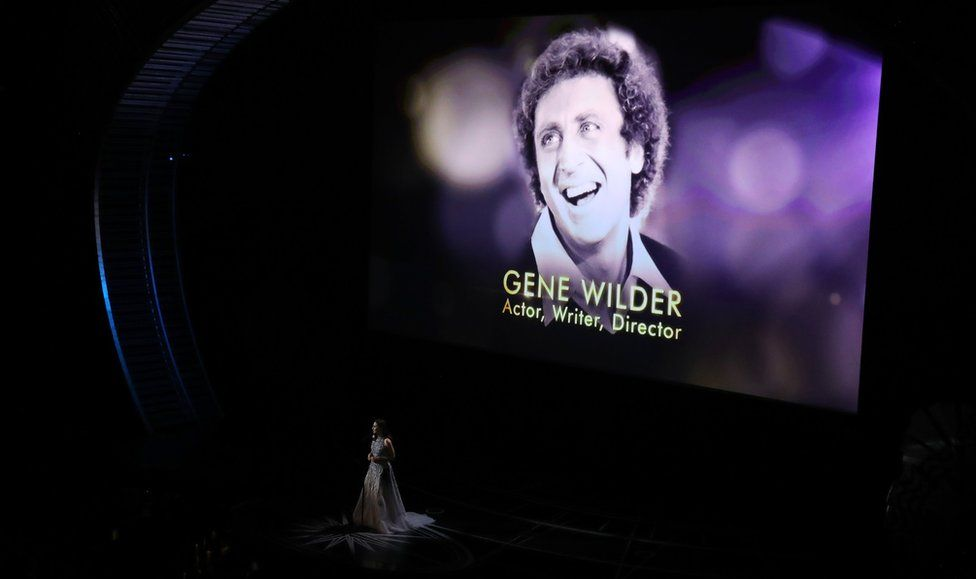 """Sara Bareilles performs during the """"In Memoriam"""" segment with an image of the late Gene Wilde"""