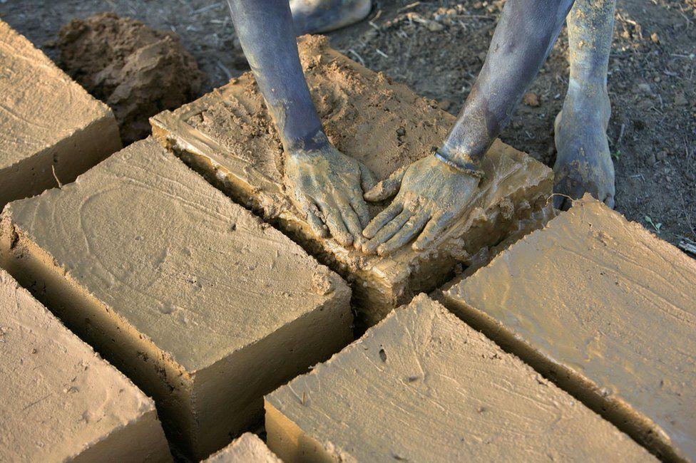 Evariste Citegetse shapes the mud bricks she will use to build her family's home in Ruyigi, Burundi