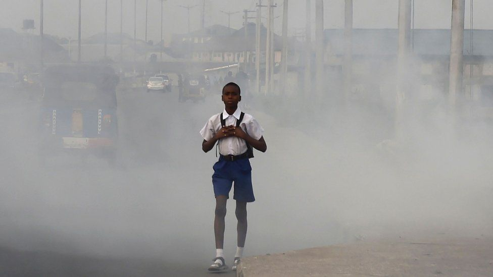 A school boy walks past smoke and fumes emitted from a dump in the city of Port Harcourt.