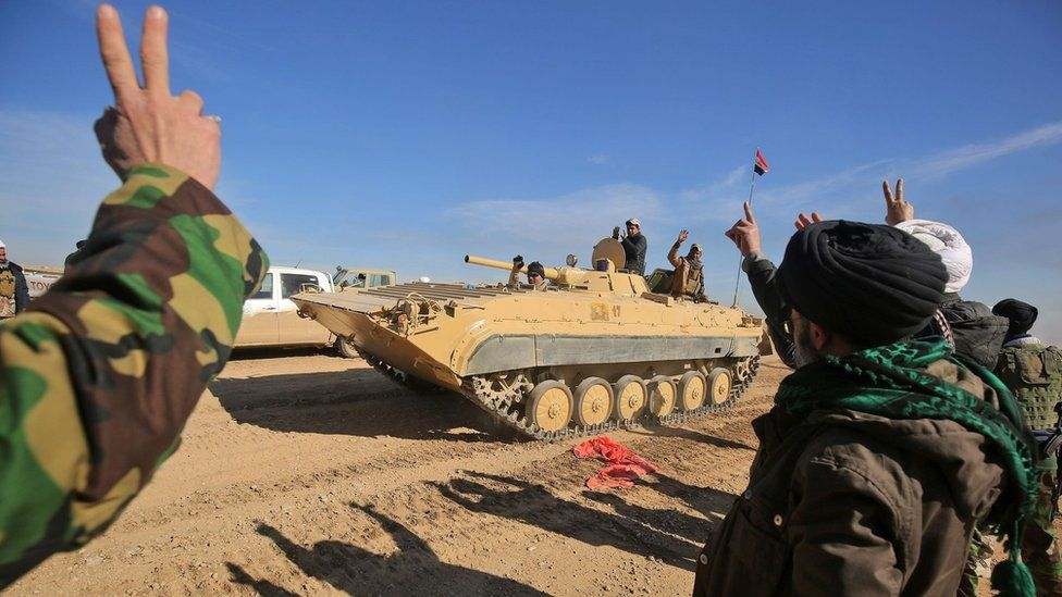 Iraqi forces, supported by Popular Mobilisation militiamen, gesture as they advance south of Mosul on 20 February 2017