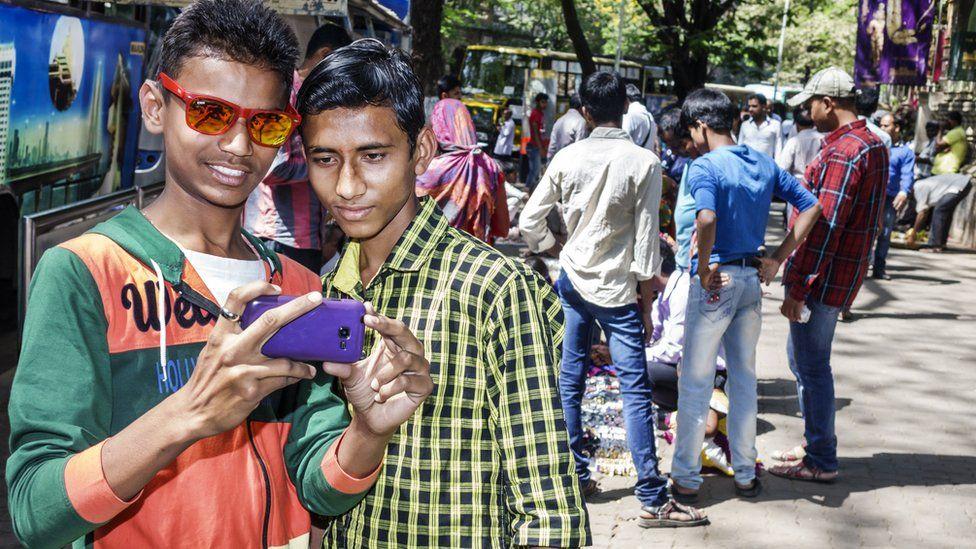 India Mumbai Fort Mumbai Kala Ghoda Mahatma Gandhi Road teen boy man friends looking smartphone.