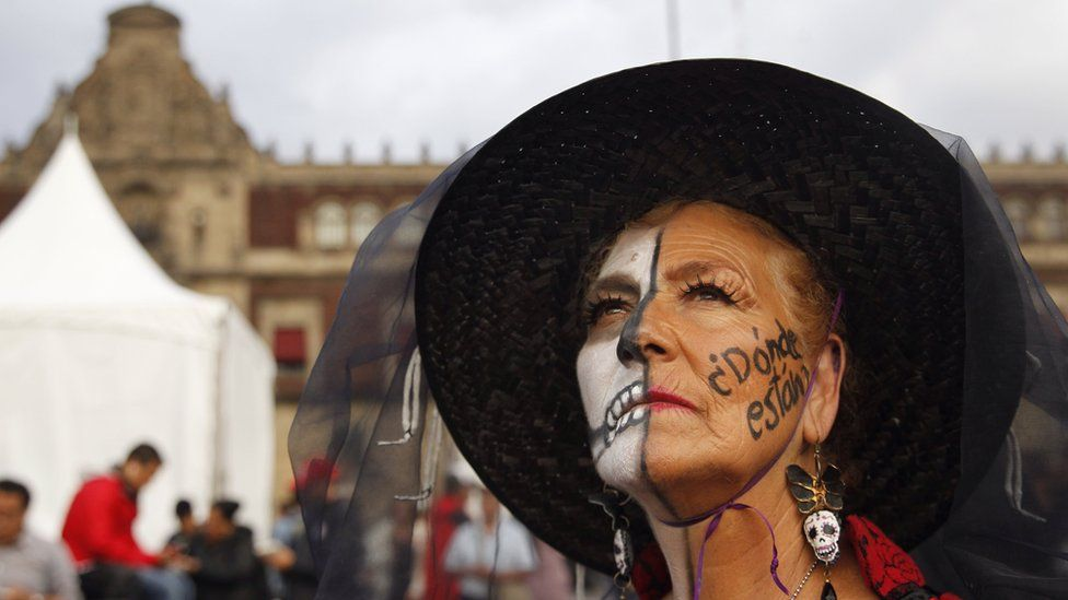 """A protester with face paint saying """"Where are they?"""" in reference to the missing 43 Ayotzinapa students"""