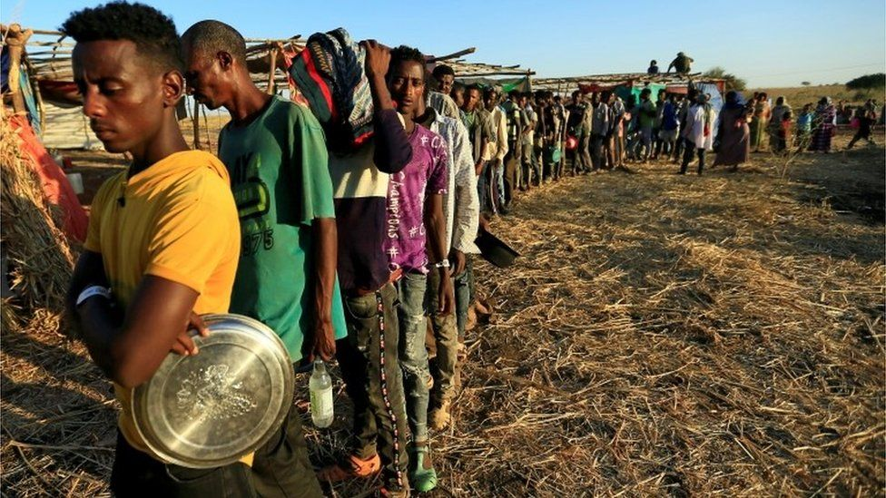 Ethiopian refugees who fled Tigray region, queue to receive food aid within the Um-Rakoba camp in Al-Qadarif state, on the border, in Sudan December 11, 2020.