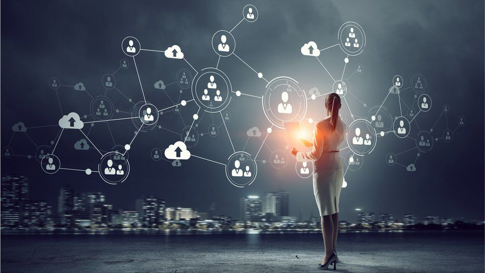 Woman standing in front of data network graphic