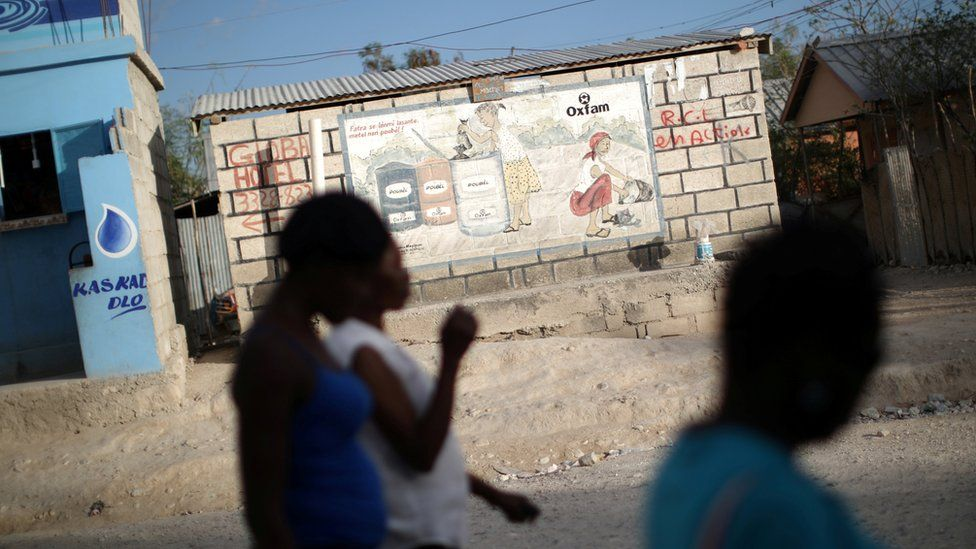 Women walk past an Oxfam sign in Corail, a camp for displaced people of the 2010 earthquake, on the outskirts of Port-au-Prince, Haiti, February 13, 2018.