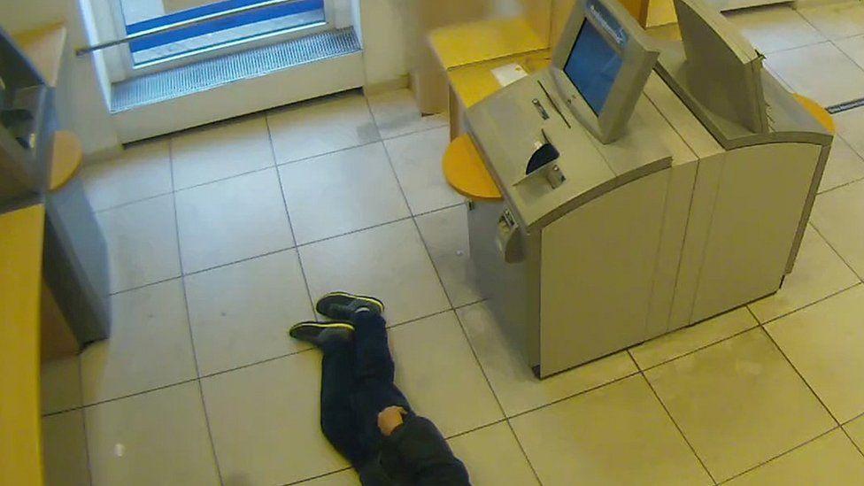 Bank CCTV shows man lying next to cash machines (Essen police photo)