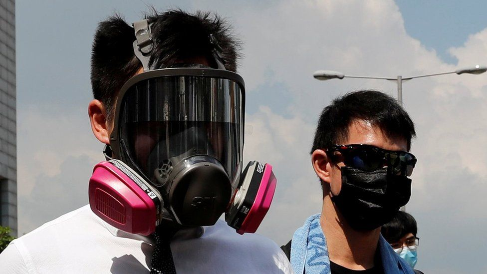Anti-government office workers wearing masks attend a lunch time protest, after local media reported on an expected ban on face masks under emergency law, at Central, in Hong Kong