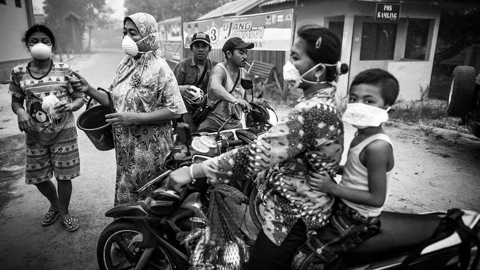Locals in Bereng Bengkel go about their daily lives wearing haze masks