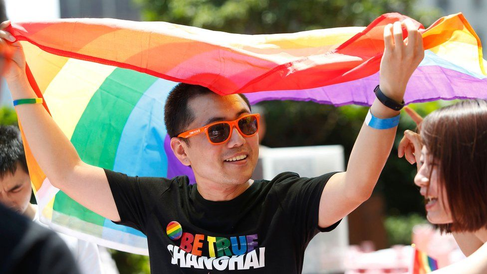 A man holds a rainbow flag after taking part in the Pride Run in Shanghai, June 2017
