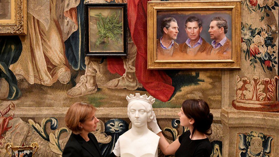 a bust before a wall of paintings