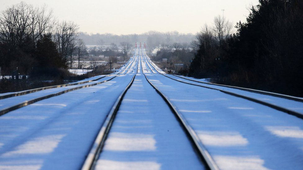Train tracks lead towards the camp of First Nations members at a railway crossing