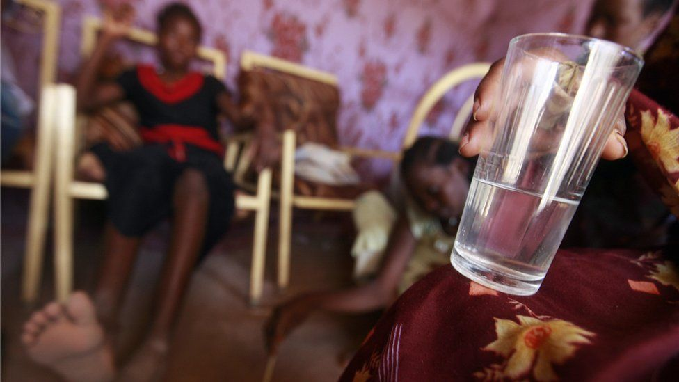 Sudanese Zakia (R), 23-years-old, who sells alcohol, holds a cup of her brew at her home in Halfaya near Khartoum on June 28, 2008.