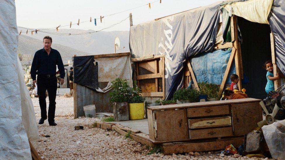 David Cameron walking through a camp housing Syrian refugee families