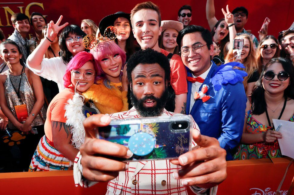 Donald Glover poses for a photo with fans