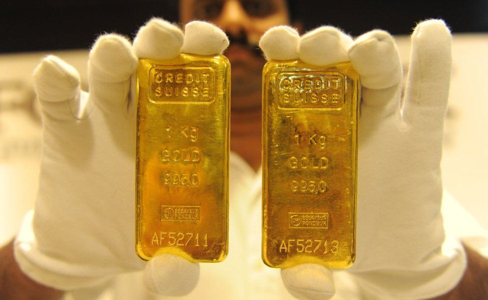 A jewellery shop employee displays 24-carat gold bars
