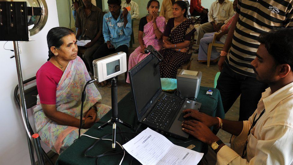 An Indian villager looks at an Iris scanner during the data collecting process for Aadhaar.
