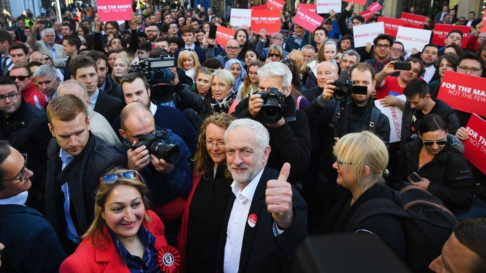 Jeremy Corbyn in the middle of a crowd, looks to the camera and raises his thumb