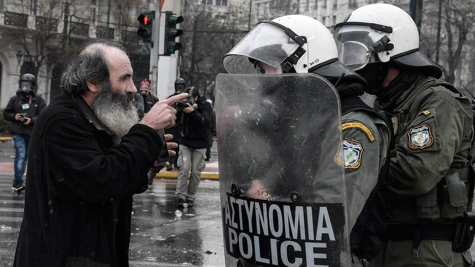 A priest argues with riot police during a demonstration against the agreement with Skopje to rename neighbouring country Macedonia as the Republic of North Macedonia, on January 20, 2019 in Athens