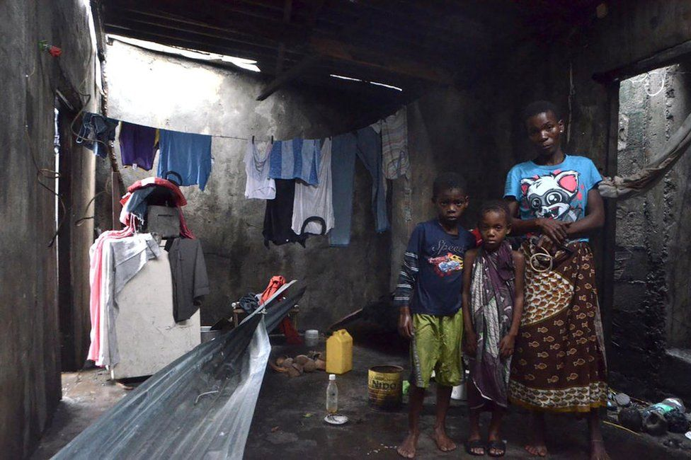 A young boy, girl and a woman take shelter in a structure on 19 March 2019 surrounded by clothes and other belongings.