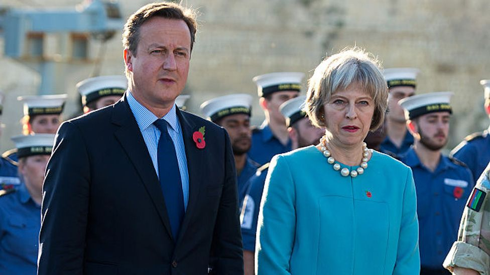 British Prime Minister David Cameron and Home Secretary Theresa May attend a remembrance service on HMS Bulwark during the Valletta Summit on migration on November 11, 2015 in Valletta, Malta