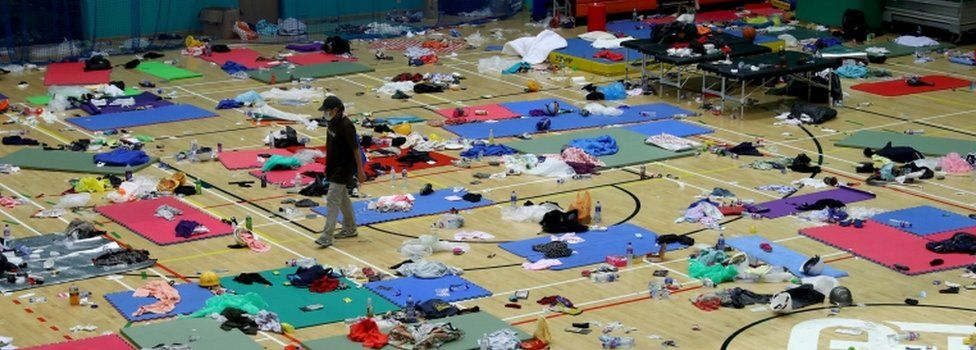 A protester walks between mats on the floor of PolyU gymnasium