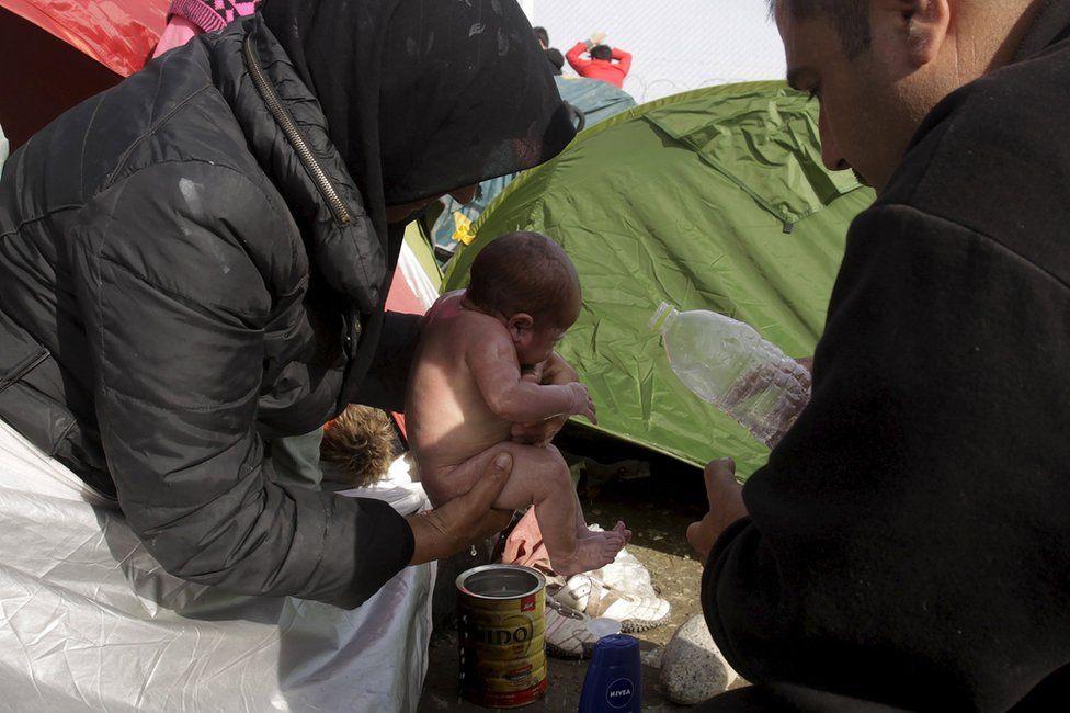 A migrant couple wash their newborn baby near Idomeni, Greece, 6 March