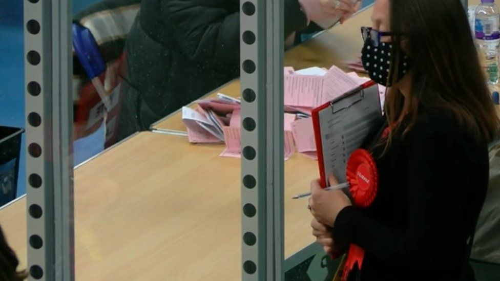 A woman with a Labour rosette at a count