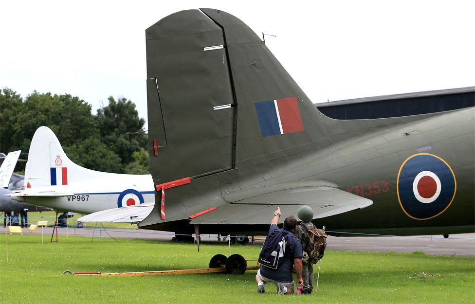 Visitors look at a vintage war plane in an outdoor museum