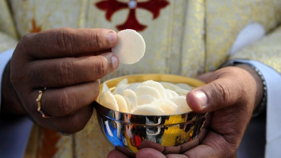 Priest holds a cup of wafers