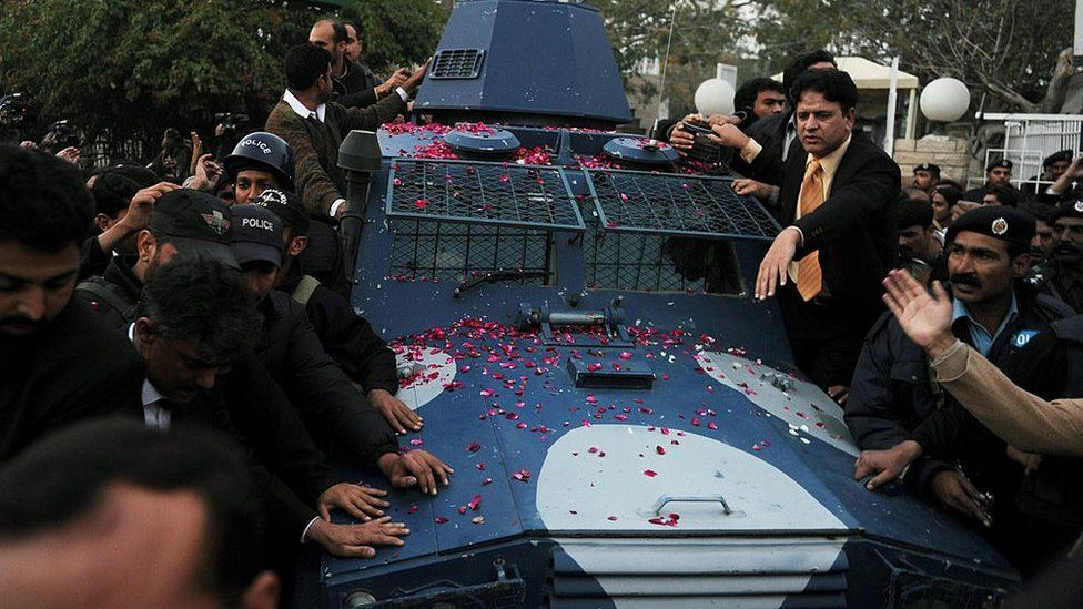 Pakistani police escort an armoured vehicle carrying arrested Pakistani bodyguard Malik Mumtaz Hussain Qadri, the alleged killer of Punjab's governor Salman Taseer, as they leave the anti-terrorist court after a hearing in Rawalpindi on 6 January 2011.