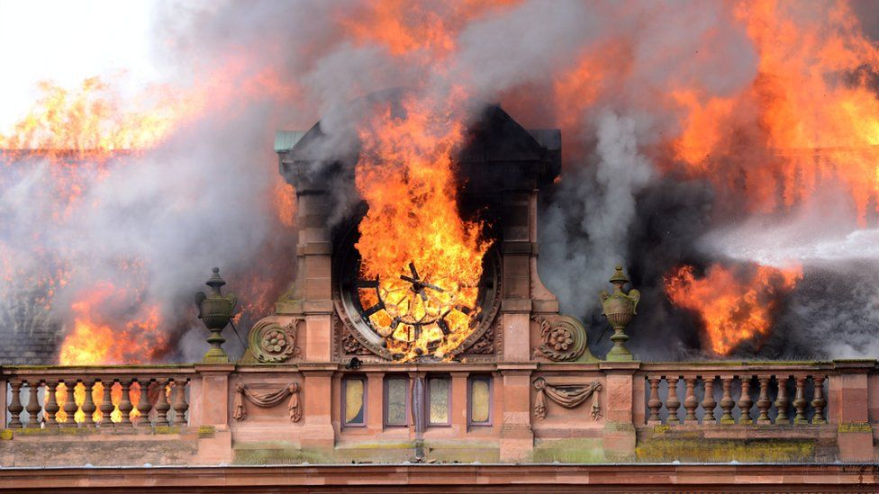 Flames destroy the clock at the top of the Bank Buildings