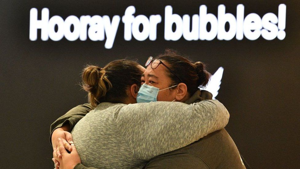 "Two women hugging next a sign that reads ""hooray for bubbles"""