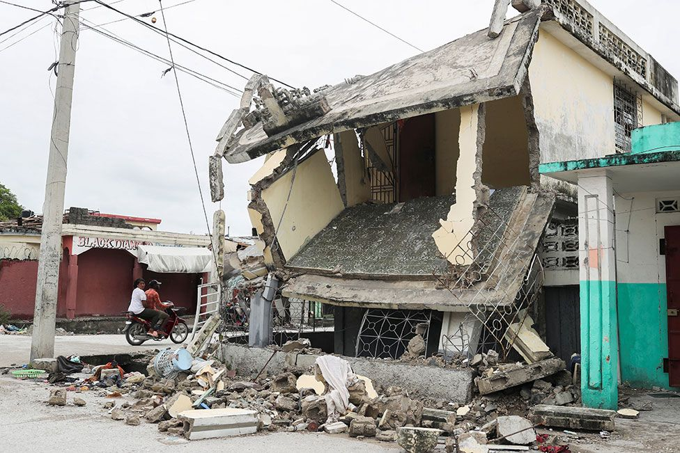 People drive in a motorcycle past a damaged home in Les Cayes, Haiti, on 17 August 2021