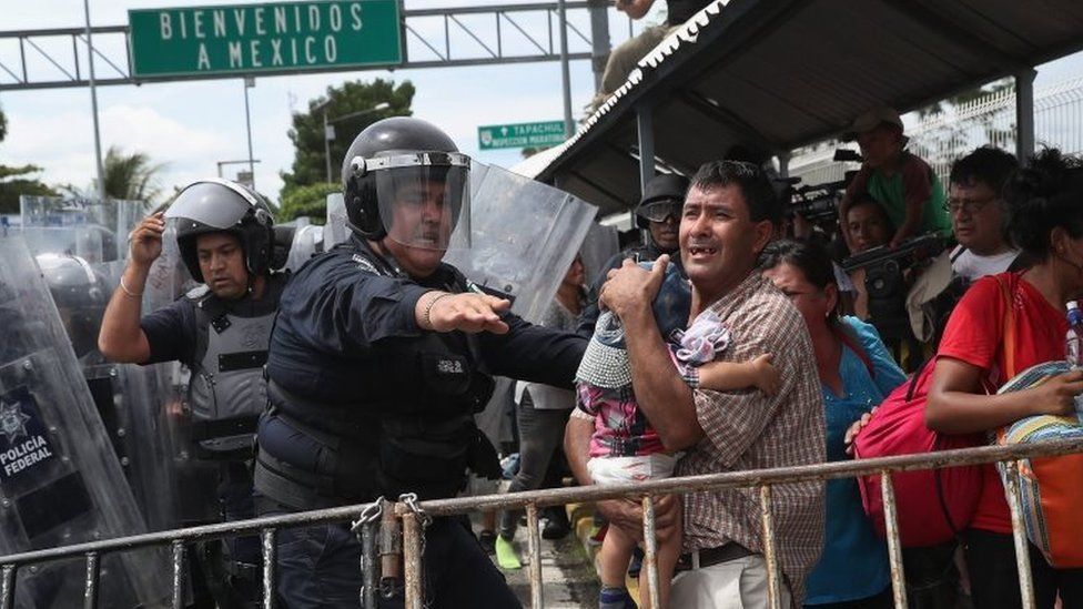 A Mexican riot policeman protects an immigrant father and child during a clash between police and the migrant caravan on the border between Mexico and Guatemala on 19 October 2018 in Ciudad Tecun Uman, Guatemala.