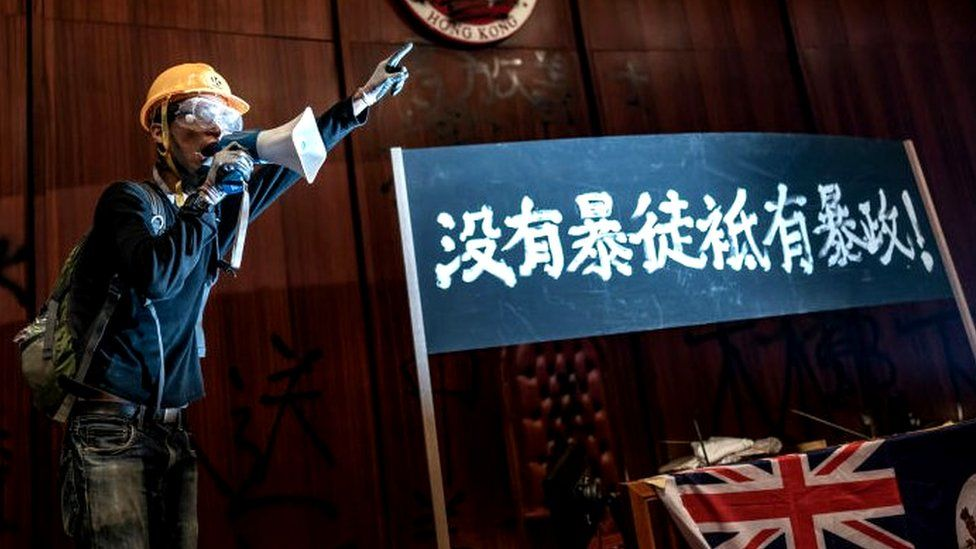 A protester talks into a megaphone after they broke into the parliament chamber of the government headquarters