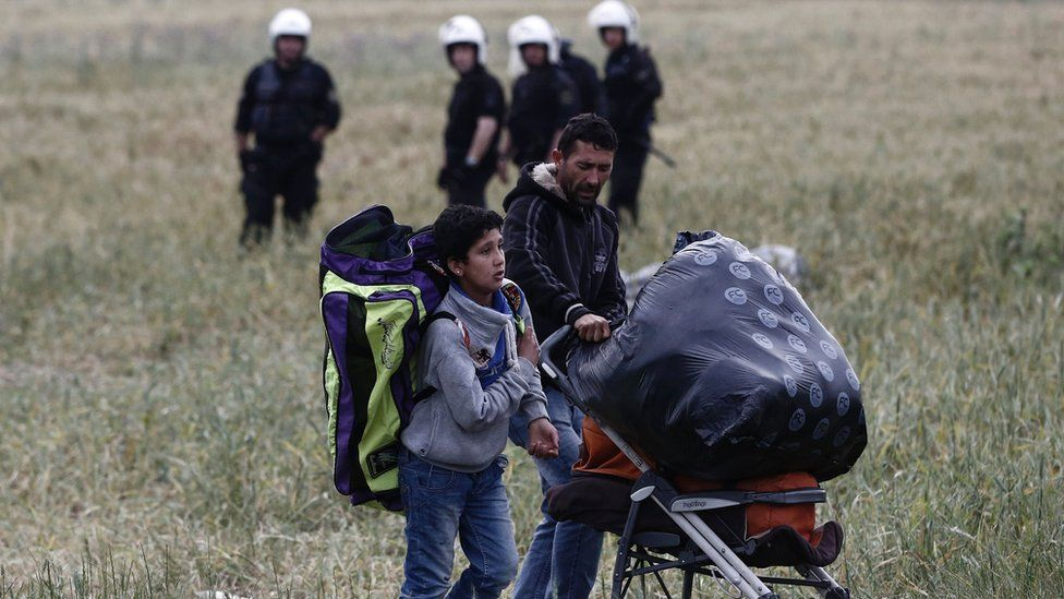 Migrants carry their belongings as they leave Idomeni camp, Greece, on 24 May 2016