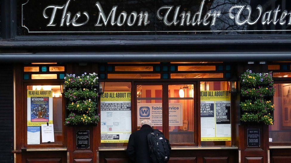 A man looks into a closed pub