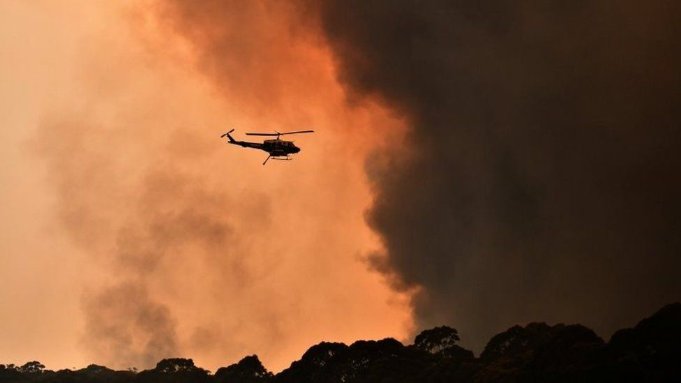 A helicopter flies near black smoke from a bushfire