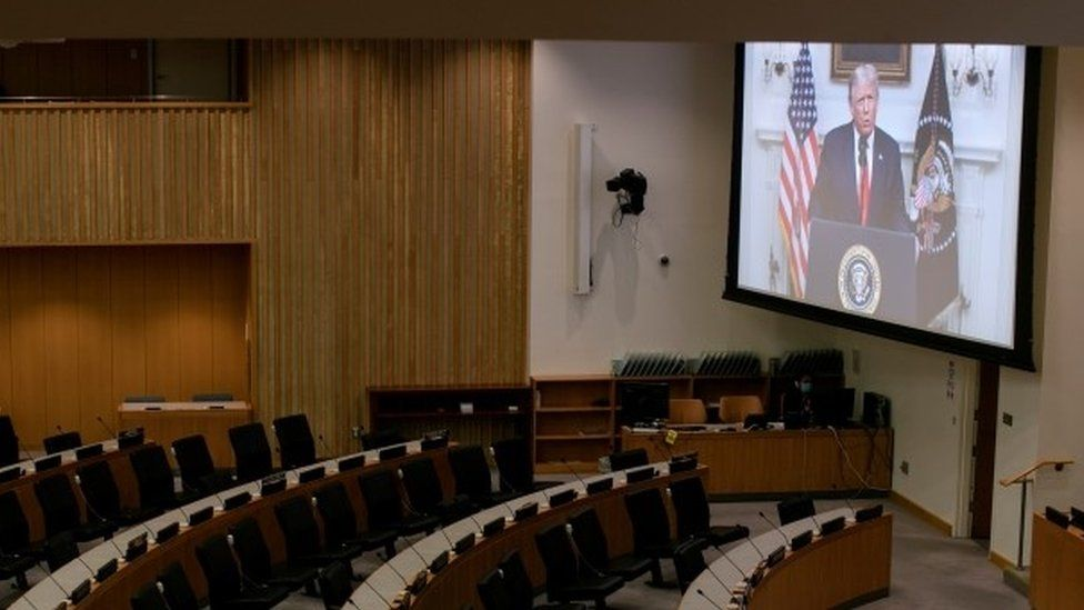 Donald Trump appears on a video screen to an empty conference room