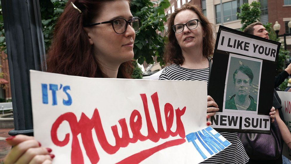Activists hold signs during a protest outside court prior to the first day of the trial of former Trump campaign chairman Paul Manafort July 31, 2018 in Alexandria, Virginia