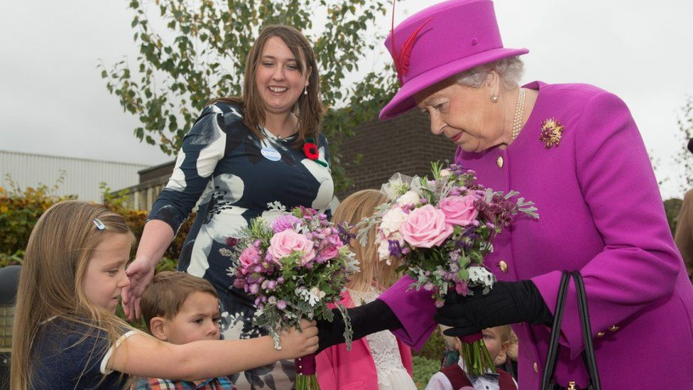 The Queen receiving posies from children during a visit to Imjin Barracks