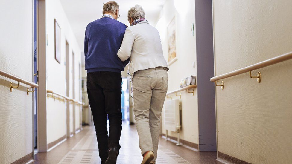 File picture of older people walking down a corridor