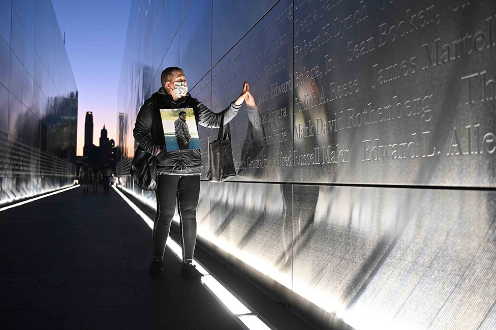 Claudia Castano touches the name of her brother German etched on a wall at the Empty Sky 9/11 Memorial in Liberty State Park in Jersey City, New Jersey, on the 20th anniversary of the terrorist attack