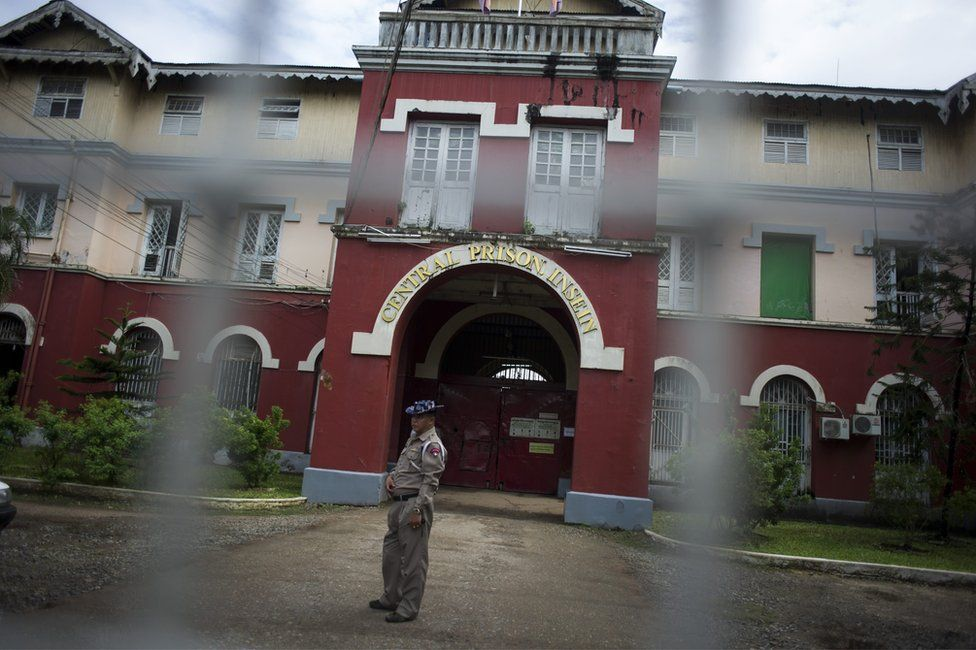 The exterior of Insein Prison, viewed through a wire fence, with a guard outside the entrance. 27 June 2016.