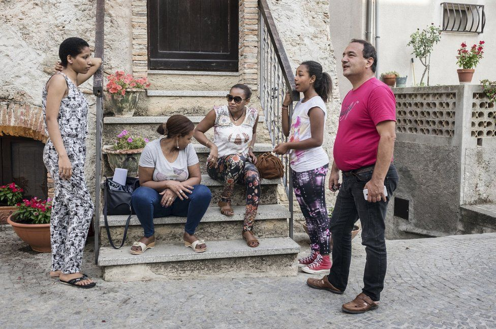 Riace's three-term mayor, Domenico Lucano chatting with a group of women from Horn of Africa