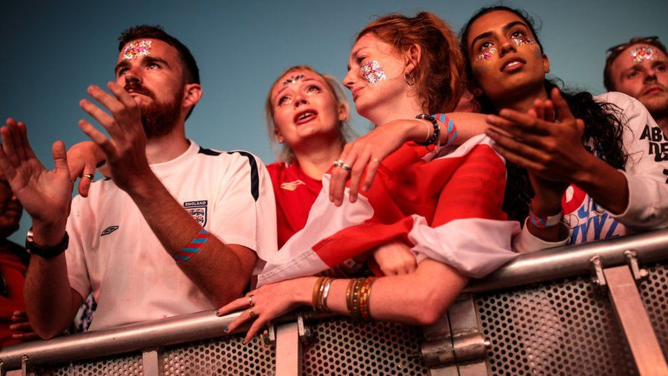 Sad England fans watch the game